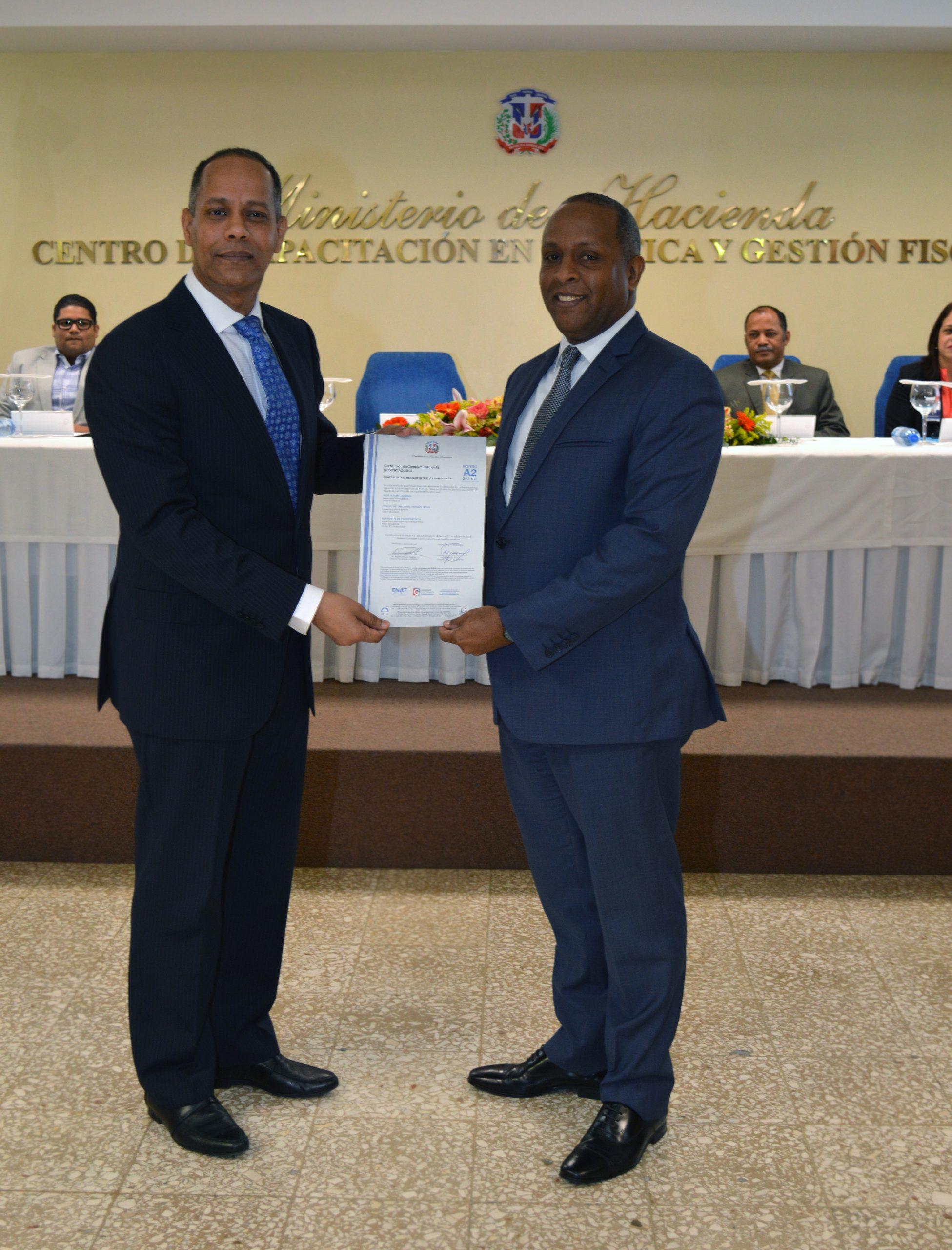 El director de la OPTIC, Armando García, entrega la certificación Nortic A2 al contralor General, Rafael Germosén.