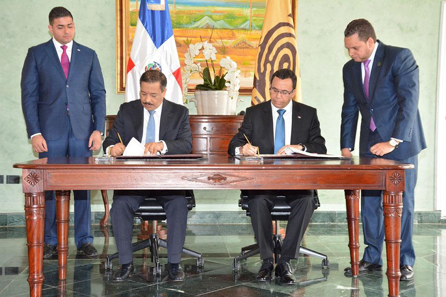Roberto Rosario, presidente de la JCE, y el canciller Andrés Navarro, durante la firma del acuerdo de colaboración para documentar a dominicanos residentes en el exterior. /GABRIEL ALCÁNTARA.