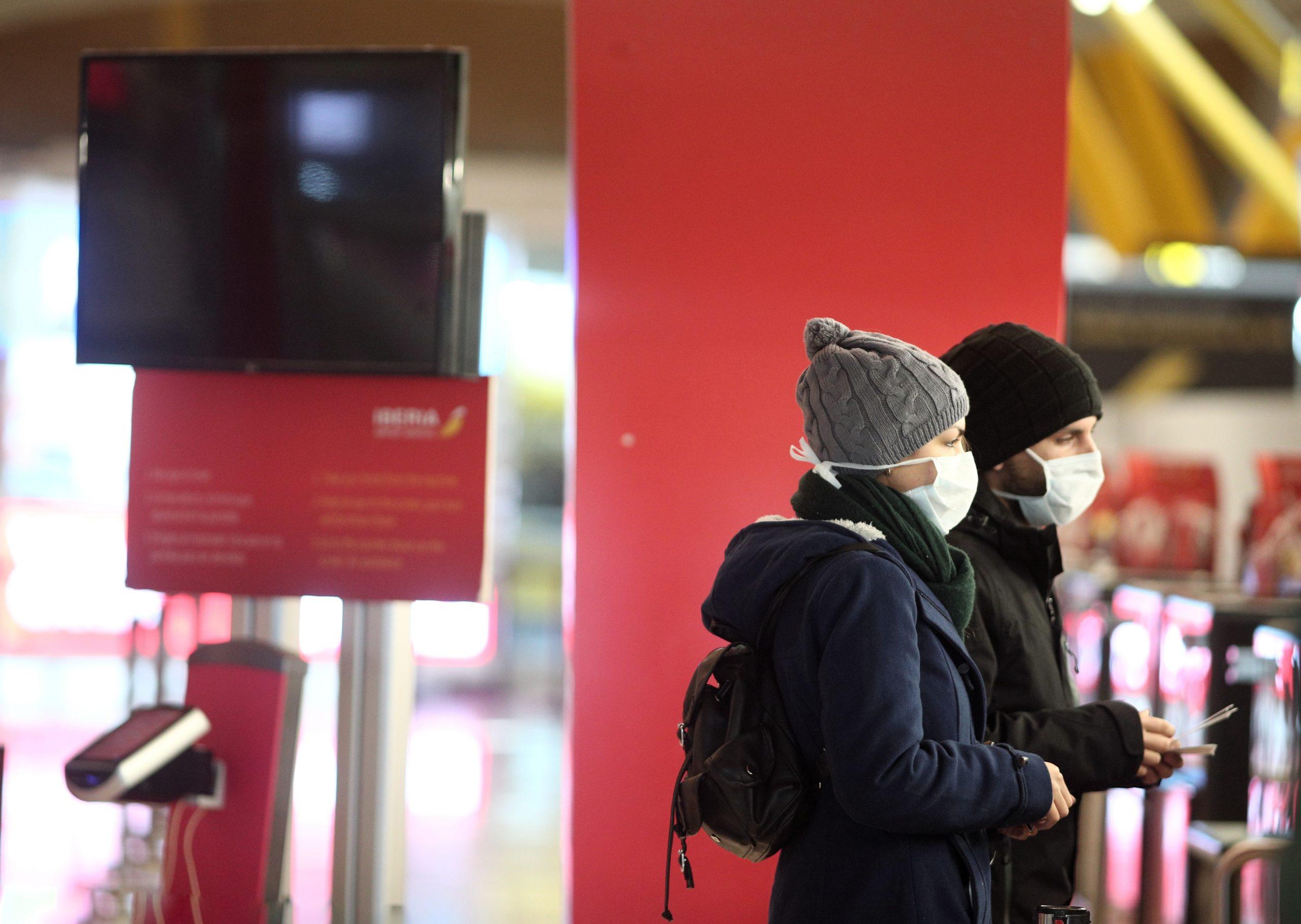 dos pasajeros protegidos con mascarilla esperan en la terminal 4 del aeropuerto adolfo suárez madrid barajas
