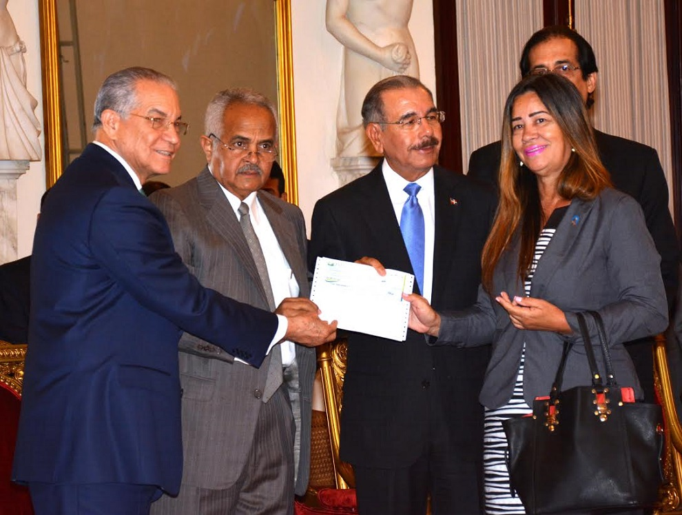 El presidente Danilo Medina entrega un cheque para la iniciativa, que constituye una alianza público-privada entre la JAD y la Dirección de Cooperación Multilateral.