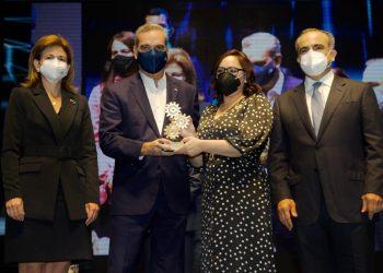 Elizabeth Mena recibe el galardón de Luis Abinader, Raquel Peña y Celso Marranzini.