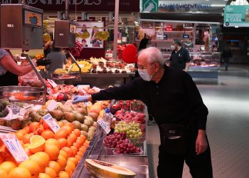 Un cliente señala la pieza de fruta que quiere en una frutería del Mercado Central de Valencia, España. | Iván Terrón,  Europa Press.