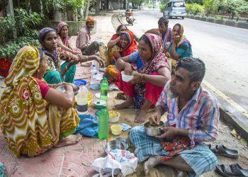 Una familia come en una calle de Bangladesh. | Munirul Alam, EFE.
