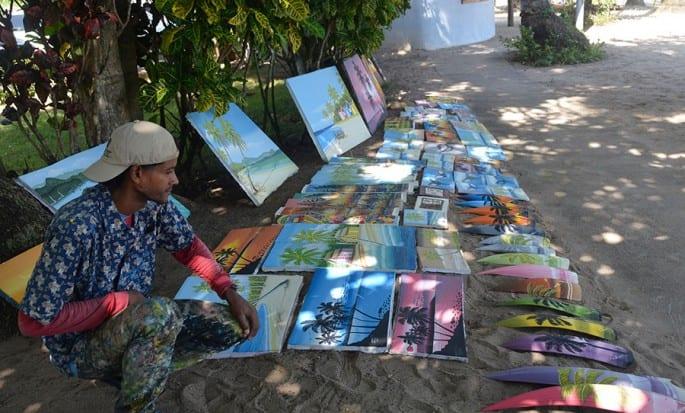 Artista exhibe sus pinturas realizadas en lienzo y yaguacil de coco.