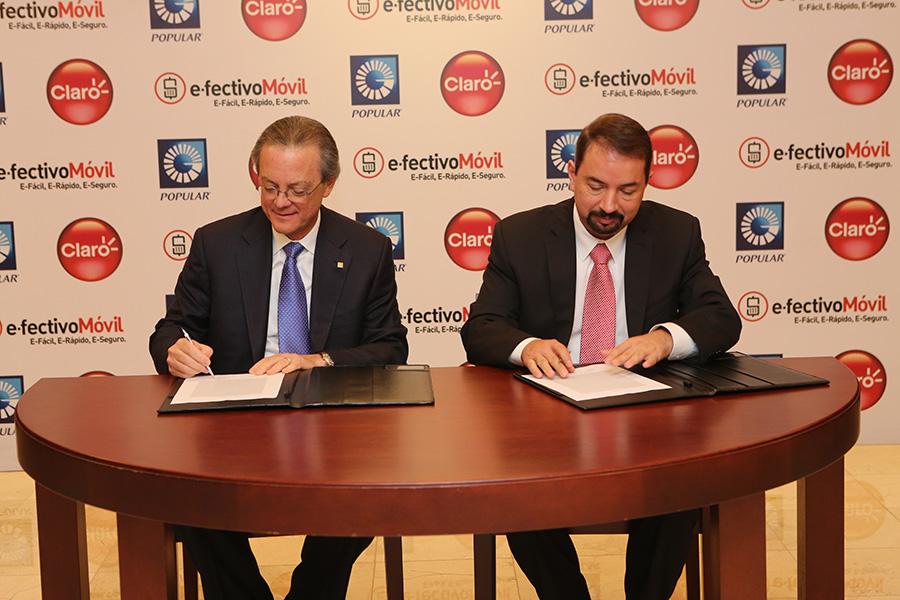 Manuel A. Grullón y Oscar Pela, durante la firma del acuerdo entre el Banco Popular y Claro para poner en vigencia el servicio e.fectivo Móvil.