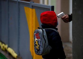 Una profesora toma la temperatura a un alumno de la Escuela Rubén Dario de Barcelona antes de entrar a clase.  | Quique Garcia, EFE.