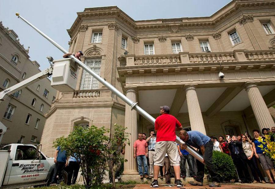 En foto de archivo, trabajadores levantan un asta de bandera en la Sección de Intereses de Cuba en Washington. | Fuente externa