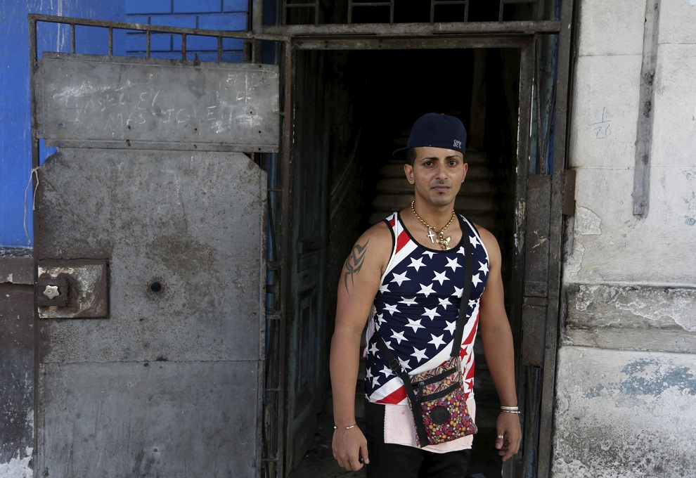 a man wearing a shirt with the u.s flag stands on a street in havana