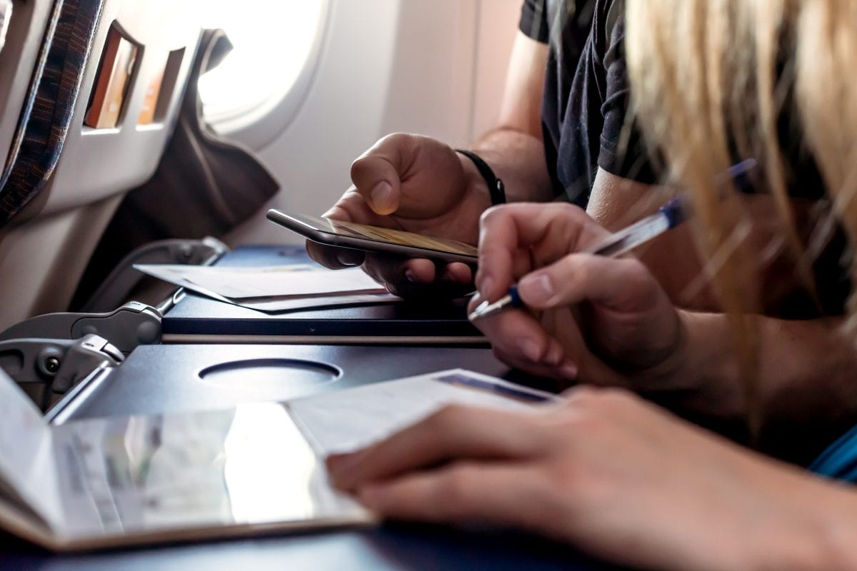 passengers filling in immigration forms in the aircraft