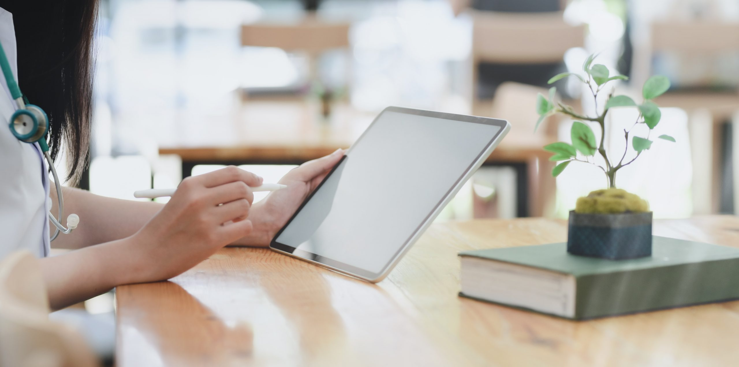 person leaning on wooden table holding white tablet 3758759